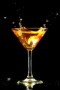alcohol splash in martini glass on black background